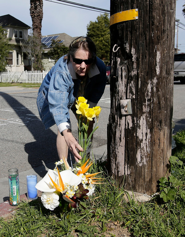 """. Gail Stolp drops flowers off at a makeshift memorial on Branciforte Ave. and Doyle St. for slain Santa Cruz police officers, detective Sgt. Loran \""""Butch\"""" Baker and detective Elizabeth Butler in Santa Cruz, Calif. on Wednesday, Feb. 27, 2013. The pair were gunned down near  this location yesterday while investigating a possible domestic violence or sexual assault when a suspect fired at them. The gunman, Jeremy Peter Goulet, was later gunned down when he exchanged gunfire with police during a manhunt. (Gary Reyes/ Staff)"""