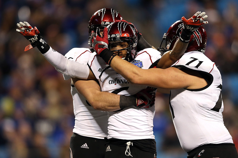 Description of . Anthony McClung #6 of the Cincinnati Bearcats celebrates with teammates after catching a touchdown during their game against the Duke Blue Devils at Bank of America Stadium on December 27, 2012 in Charlotte, North Carolina.  (Photo by Streeter Lecka/Getty Images)