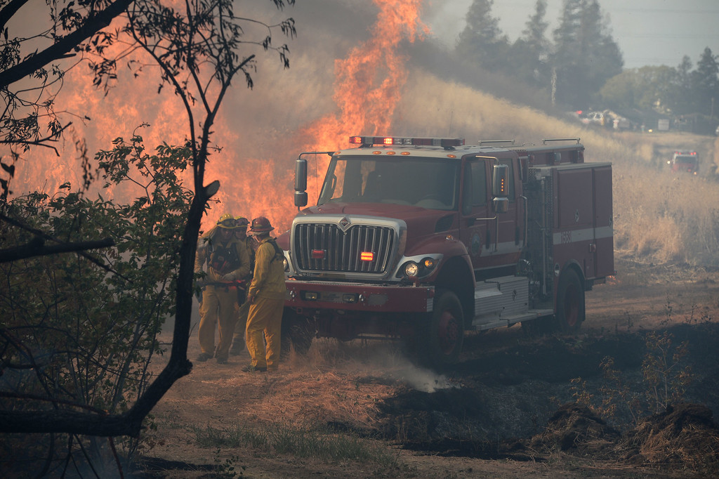 . Firefighters begin to lay a fire hose where the blaze heads up a hillside near the end of Foothill Drive in Antioch, Calif., on Wednesday, June 24, 2015. (Susan Tripp Pollard/Bay Area News Group)