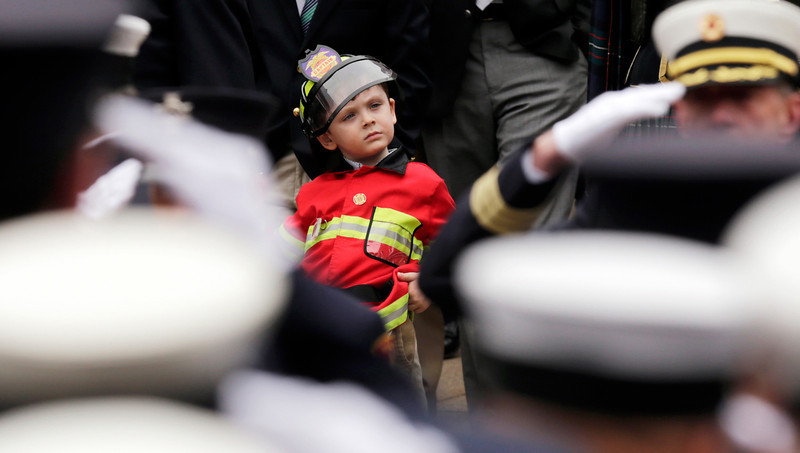 . Firefighters salute as Robbie Malone watches as the casket of his uncle, Boston Fire Lt. Edward Walsh is lifted onto Engine 33 as the funeral procession prepares to depart from St. Patrick\'s Church in Watertown, Mass., Wednesday, April 2, 2014. Walsh and his colleague Michael Kennedy died after being trapped while battling a nine-alarm apartment fire in Boston on March 26. (AP Photo/Charles Krupa)
