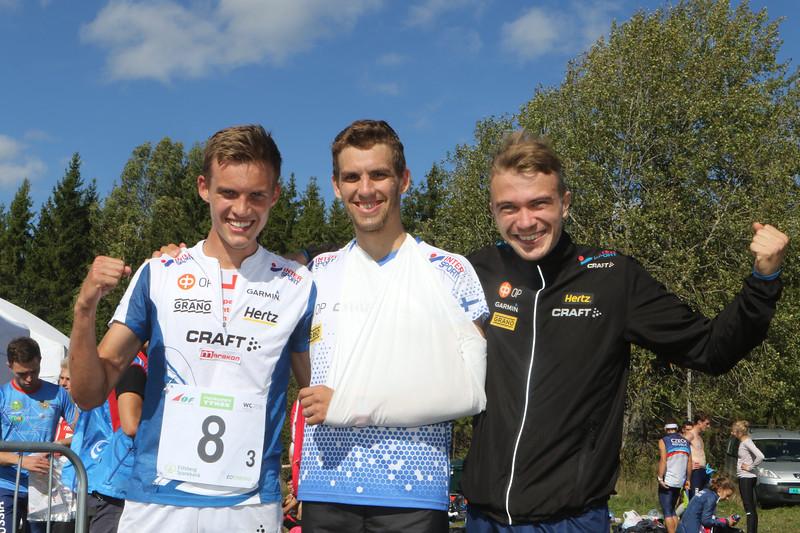 Aleksi Niemi (vas.), olkapäänsä loukannut Fredric Portin ja Miika Kirmula, maailmancupin viestissä 4.