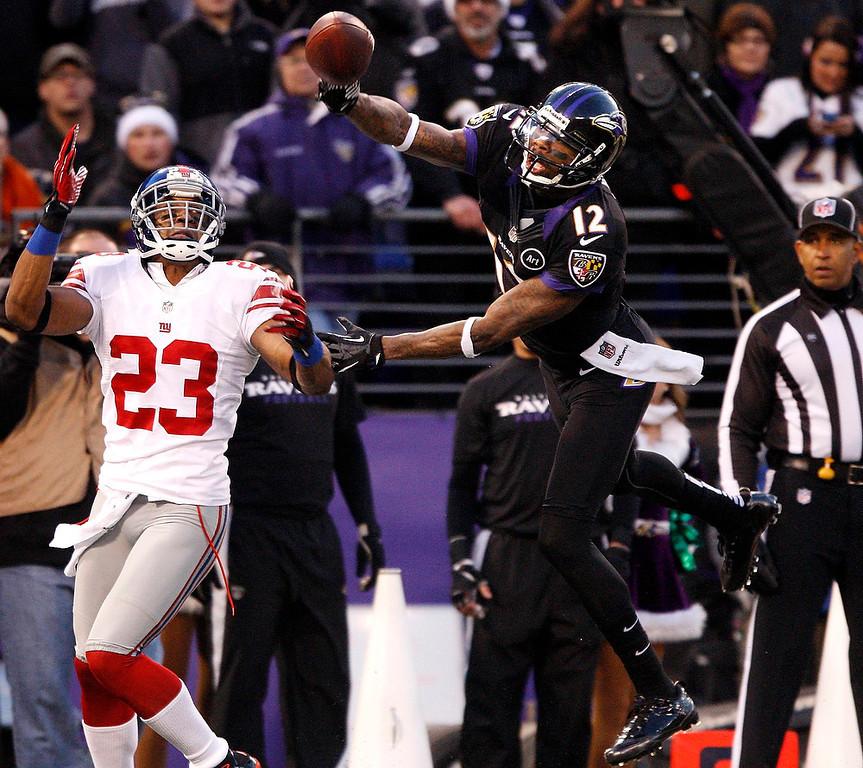. Baltimore Ravens receiver Jacoby Jones (12) fails to make a catch while defended by New York Giants cornerback Corey Webster (23) during the first half of their NFL football game in Baltimore, Maryland, December 23, 2012. REUTERS/Jonathan ErnsT