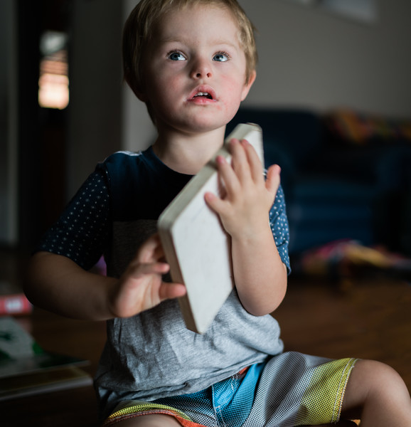 Preschool Boy holding a Book while Seated on Floor
