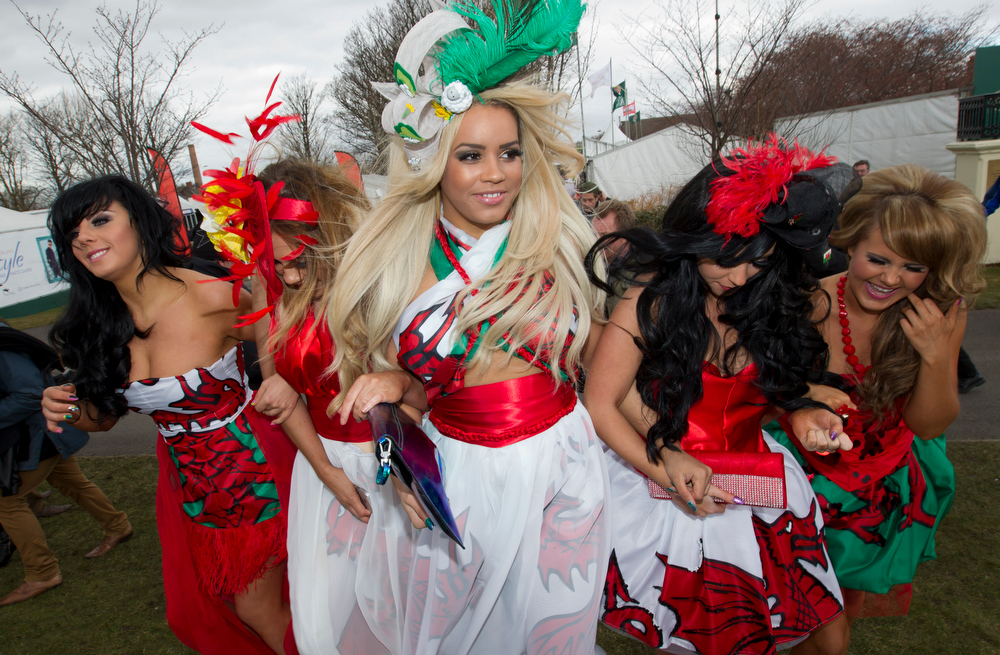 . A group of women laugh as they pose for photographers during Ladies\' Day at Aintree Racecourse in Liverpool, England, Friday, April 5, 2013. (AP Photo/Jon Super)