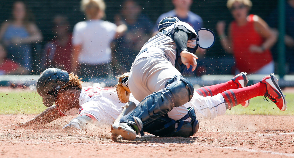 . Cleveland Indians\' Jose Ramirez scores past New York Yankees\' Kyle Higashioka on a sacrifice fly by Yan Gomes during the eighth inning of a baseball game, Sunday, July 15, 2018, in Cleveland. The Indians beat the Yankees 5-2. (AP Photo/Ron Schwane)