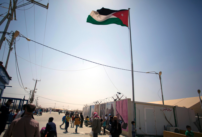 . In this Thursday April 17, 2014 photo, the Jordanian flag waves over the main entrance to Zaatari refugee camp near the Syrian border in Jordan. Some residents, frustrated with Zaatari, the region\'s largest camp for Syrian refugees, set up new, informal camps on open lands, to escape tensions and get closer to possible job opportunities.(AP Photo/Khalil Hamra)