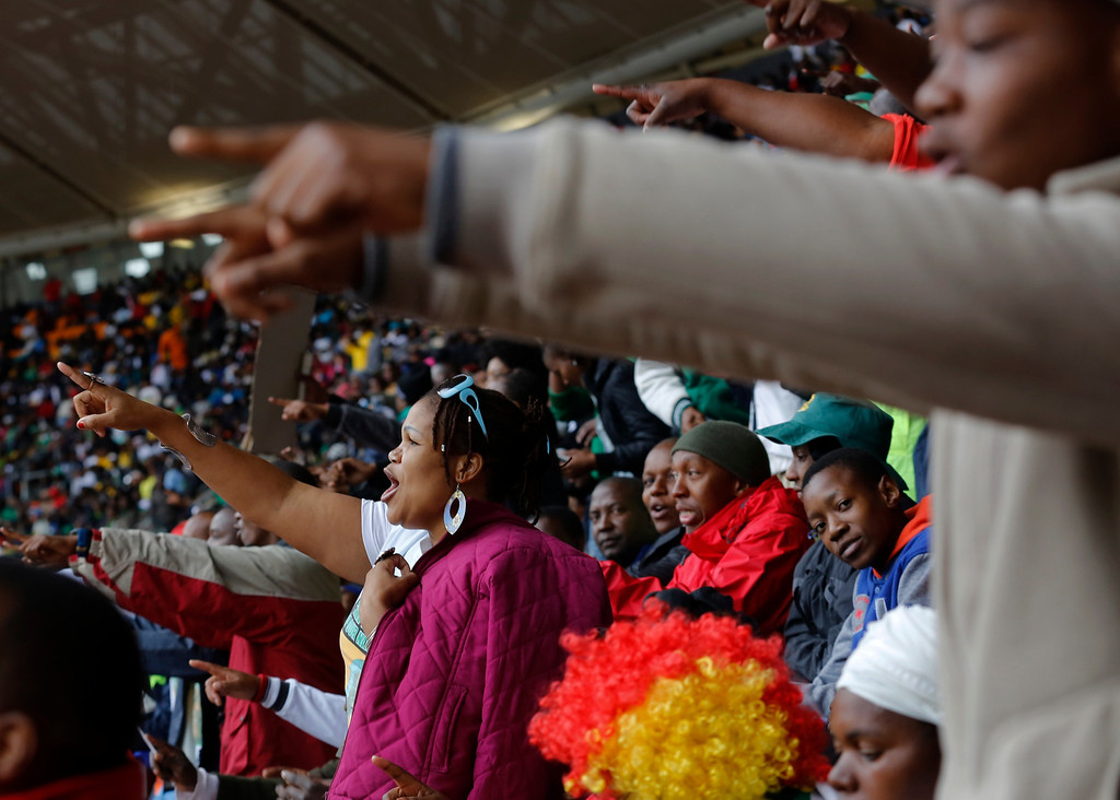 . People sing songs during the memorial service for former South African president Nelson Mandela at the FNB Stadium in Soweto near Johannesburg, Tuesday, Dec. 10, 2013. (AP Photo/Markus Schreiber)