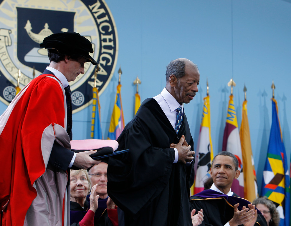 . Jazz musician Ornette Coleman, center, stands to receive an honorary Doctor of Music degree as President Barack Obama looks on at the University of Michigan commencement ceremony in Ann Arbor, Saturday, May 1, 2010. (AP Photo/Charles Dharapak)