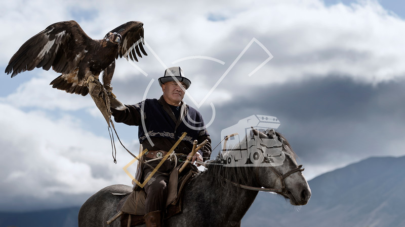Kyrgyz man on a horse posing with his hunting eagle outdoors in Kyrgyzstan.