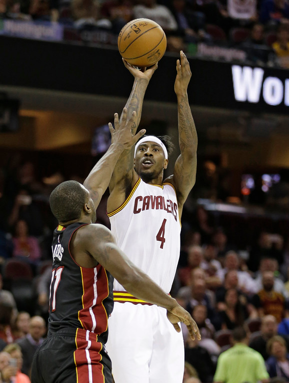 . Cleveland Cavaliers\' Iman Shumpert (4) shoots over Miami Heat\'s Dion Waiters (11) in the first half of an NBA basketball game, Monday, March 6, 2017, in Cleveland. (AP Photo/Tony Dejak)