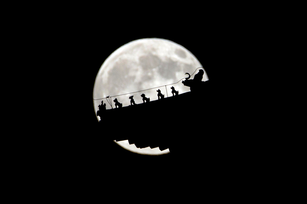 ". A perigee moon also known as a supermoon rises behind figurines on a Chinese pavilion in Beijing, China, Saturday, July 12, 2014.  The phenomenon, which scientists call a ""perigee moon,\"" occurs when the moon is near the horizon and appears larger and brighter than other full moons. (AP Photo/Ng Han Guan)"