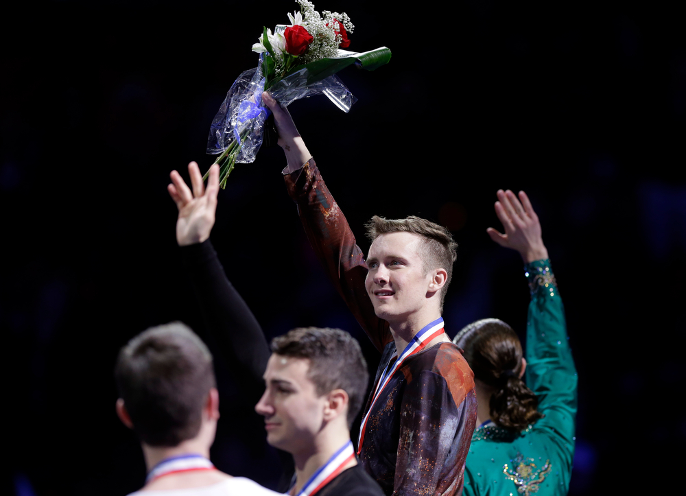 . First place winer Jeremy Abbott, third from left, stands with the other three top mens skaters, from the left, Joshua Farris, fourth place, Max Aaron, third place, and Jason Brown, second place, obscured at right, as they pose on the awards stand at the medals ceremony at the U.S. Figure Skating Championships, Sunday, Jan. 12, 2014 in Boston. (AP Photo/Steven Senne)
