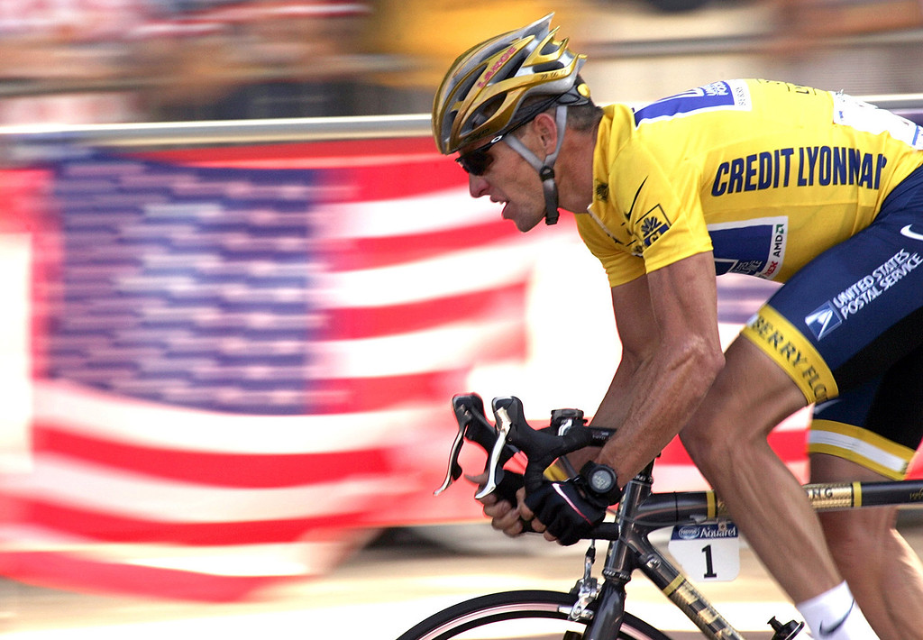 . Overall leader Lance Armstrong, of Austin, Texas, rides down the Champs Elysees avenue past U.S. flags during the 20th and last stage of the Tour de France cycling race between Montereau, southeast of Paris, and the Champs-Elysees in Paris on July 25, 2004. Federal prosecutors said, Friday, Feb. 3, 2012, they are closing a criminal investigation of Armstrong and will not charge him over allegations the seven-time Tour de France winner used performance-enhancing drugs. (AP Photo/Franck Prevel, File)