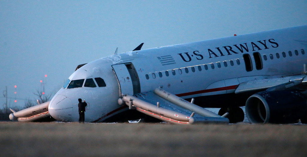 . A person takes a photo of a damaged US Airways jet at the end of a runway at the Philadelphia International Airport, Thursday, March 13, 2014, in Philadelphia. Airline officials said the flight was heading to Fort Lauderdale, Fla., when the pilot was forced to abort takeoff around 6:30 p.m., after the front landing gear failed. An airport spokeswoman said no injuries have been reported. (AP Photo/Matt Slocum)