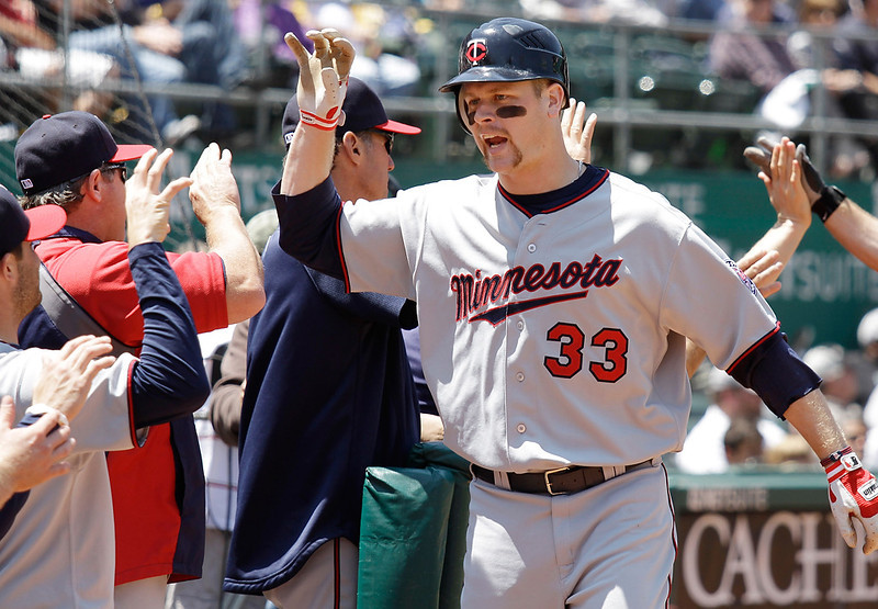 . The Twins\' Justin Morneau (33) is greeted at the dugout after hitting a two-run home run against the Oakland Athletics during the fifth inning of their game in Oakland, Calif., Thursday, May 19, 2011. Minnesota won the game 11-1. (AP Photo/Eric Risberg)