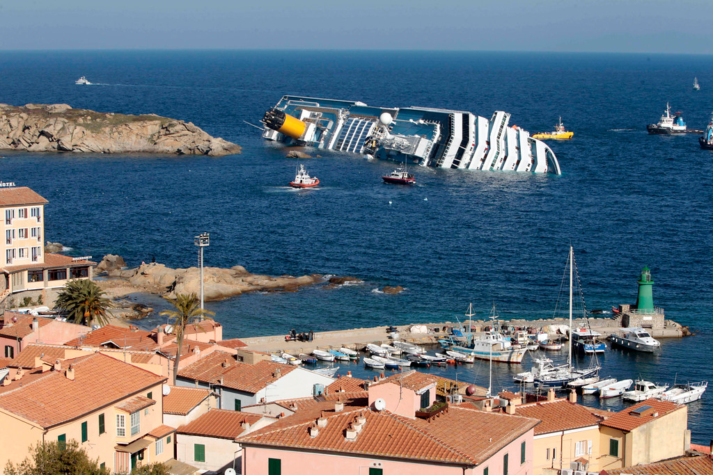 . FILE - This Jan. 14, 2012 file photo shows the luxury cruise ship Costa Concordia leaning on its starboard side after running aground on the tiny Tuscan island of Giglio, Italy. Franco Gabrielli, who heads the Civil Protection Department overseeing the wreck\'s removal, told reporters on Giglio Island Sunday, July 13, 2014, that while weather conditions aren\'t optimal, they are good enough to permit the start of operations to refloat and tow the Concordia to Genoa on the mainland for scrapping. He also promised that a search will be conducted for the only unrecovered body of the 32 Costa Concordia shipwreck victims as soon as the wrecked cruise liner is towed away from the island where it struck a reef in 2012. (AP Photo/Gregorio Borgia, File)