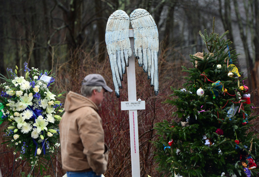 Description of . A man walks by a makeshift shrine to the victims of an elementary school shooting in Newtown, Connecticut, December 17, 2012. Funerals began Monday in the little Connecticut town of Newtown after the school massacre that took the lives of 20 small children and six staff, triggering new momentum for a change to America's gun culture. The first burials, held under raw, wet skies, were for two six-year-old boys who were among those shot in Sandy Hook Elementary School. On Tuesday, the first of the girls, also aged six, was due to be laid to rest. There were no Monday classes at all across Newtown, and the blood-soaked elementary school was to remain a closed crime scene indefinitely, authorities said. AFP PHOTO/Emmanuel DUNAND  DUNAND/AFP/Getty Images