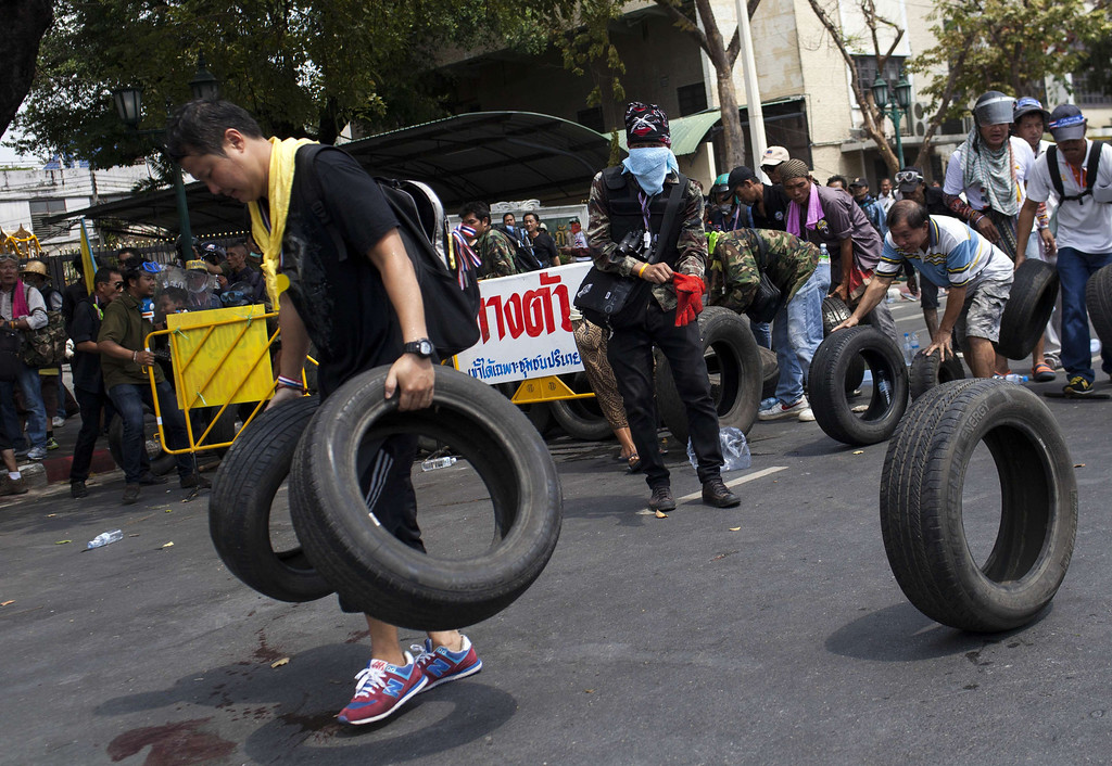 . Anti-government protesters carry tires next to pools of blood from an injured protester as they move their barricade closer to the police\'s position during clashes in Bangkok on February 18, 2014.  AFP PHOTO / KC Ortiz/AFP/Getty Images