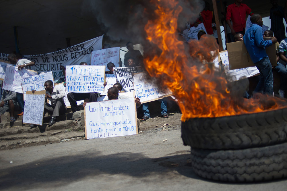 Description of . Congolese demonstrators holding placards criticising the government and the United Nations sit beside a burning tyre in Goma on December 6, 2012 as a small group of youth activists demonstrates, protesting the inaction of the UN and the government, after M23 rebels took the city on November 20. Rebels in the Democratic Republic of Congo will start talks with Kinshasa's government in Kampala on December 7, to