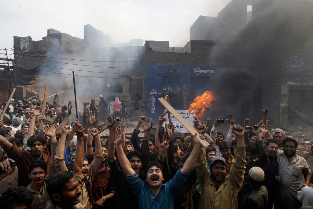 """. An angry mob reacts after burning Christian houses in Lahore, Pakistan, Saturday, March 9, 2013. A mob of hundreds of people in the eastern Pakistani city of Lahore attacked a Christian neighborhood Saturday and set fire to homes after hearing accusations that a Christian man had committed blasphemy against Islam\'s prophet Mohammed, said a police officer. Placard center reads, \"""" Blasphemer is liable to death.\"""" (AP Photo/K.M. Chaudary)"""