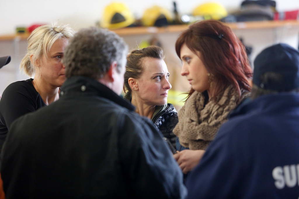 . Neighbors gather at the Oso Fire Department to look for updates about the fatal mudslide that washed over homes and over Highway 530 east of Oso, Wash., Saturday, March 22, 2014. Highway 530 was closed in both directions, and authorities confirmed at least 2 fatalities by Saturday afternoon. (AP Photo /The Daily Herald, Annie Mulligan)
