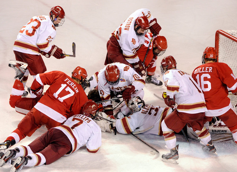 . Denver goalie Juho Olkinuora smothered the puck and then was buried under players from both teams in the third period. The University of Denver hockey team defeated Cornell 2-1 at Magness Arena Saturday night, January 5, 2013. Karl Gehring/The Denver Post