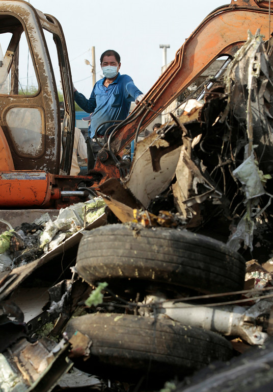 . An emergency worker surveys the wreckage at the scene of crashed TransAsia Airways Flight GE222 on the outlying island of Penghu, Taiwan, Thursday, July 24, 2014.  (AP Photo/Wally Santana)
