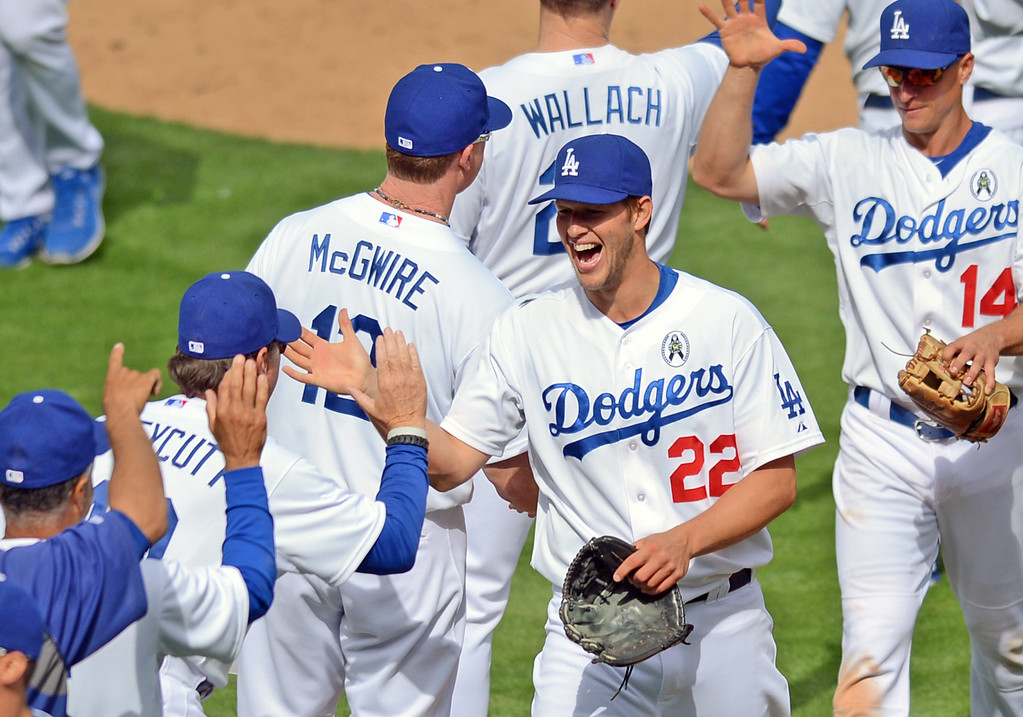 . Clayton Kershaw high fives teammates after his complete game shutout against the Giants on opening day at Dodger Stadium April 1, 2013.  Kershaw also a hit a homerun during the 4-0 victory.(Andy Holzman/Staff Photographer)