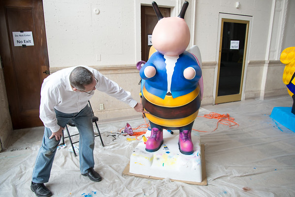 04/30/19 Wesley Bunnell | Staff Project Manager Stephen Hard of the Bees Across New Britain art event points to details on the bee being painted by artist James D'Amore which is titled Erin Stewart Worker Bee at the project headquarters at 55 West Main St on Tuesday afternoon.