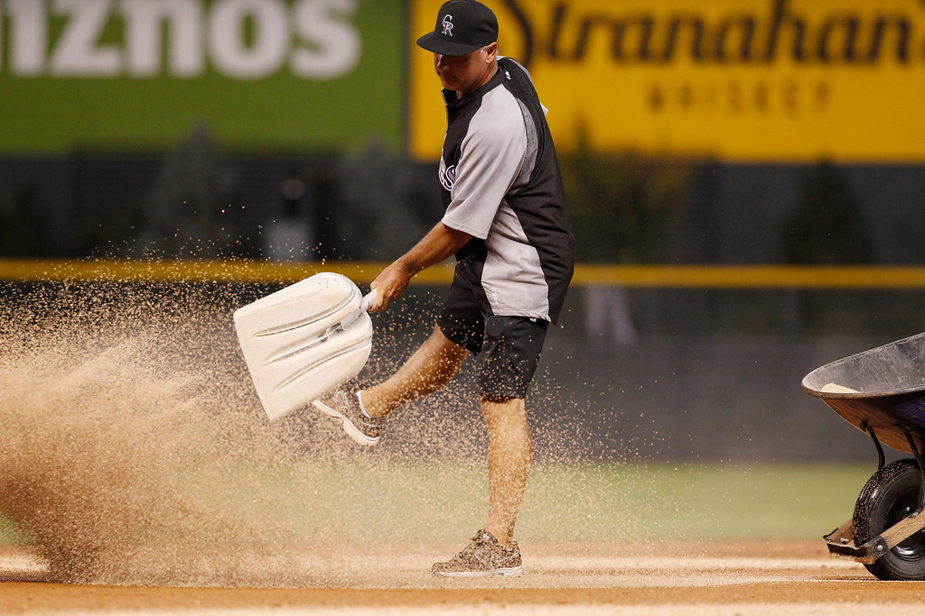 . Head groundskeeper Mark Razum throws a shovel of absorbent on the infield between the seventh and eighth innings of a baseball game between the Milwaukee Brewers and the Colorado Rockies in Denver on Saturday, July 27, 2013. Umpires stopped the game as the Rockies were coming up in the bottom of the ninth inning as rain swept in to the Denver metropolitan area -- again. (AP Photo/David Zalubowski)