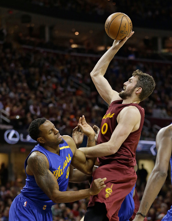 . Golden State Warriors\' Andre Iguodala, left, fouls Cleveland Cavaliers\' Kevin Love in the first half of an NBA basketball game, Sunday, Dec. 25, 2016, in Cleveland. (AP Photo/Tony Dejak)
