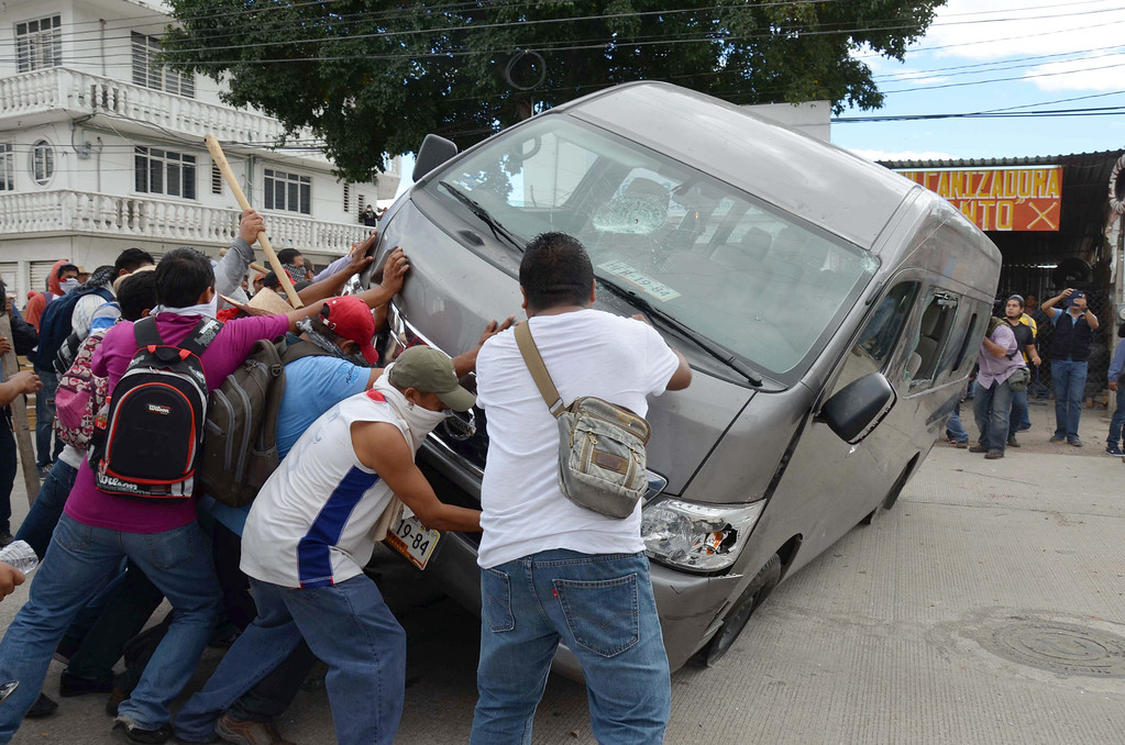 . Teachers flip a vehicle during a clash with riot police in Chilpancingo, Mexico, Tuesday, Nov. 11, 2014. Supporters of the missing 43 college rural students, refusing to believe they are dead, have kept up the protests that have blocked major highways and set government buildings ablaze in recent weeks. T(AP Photo/Alejandrino Gonzalez)