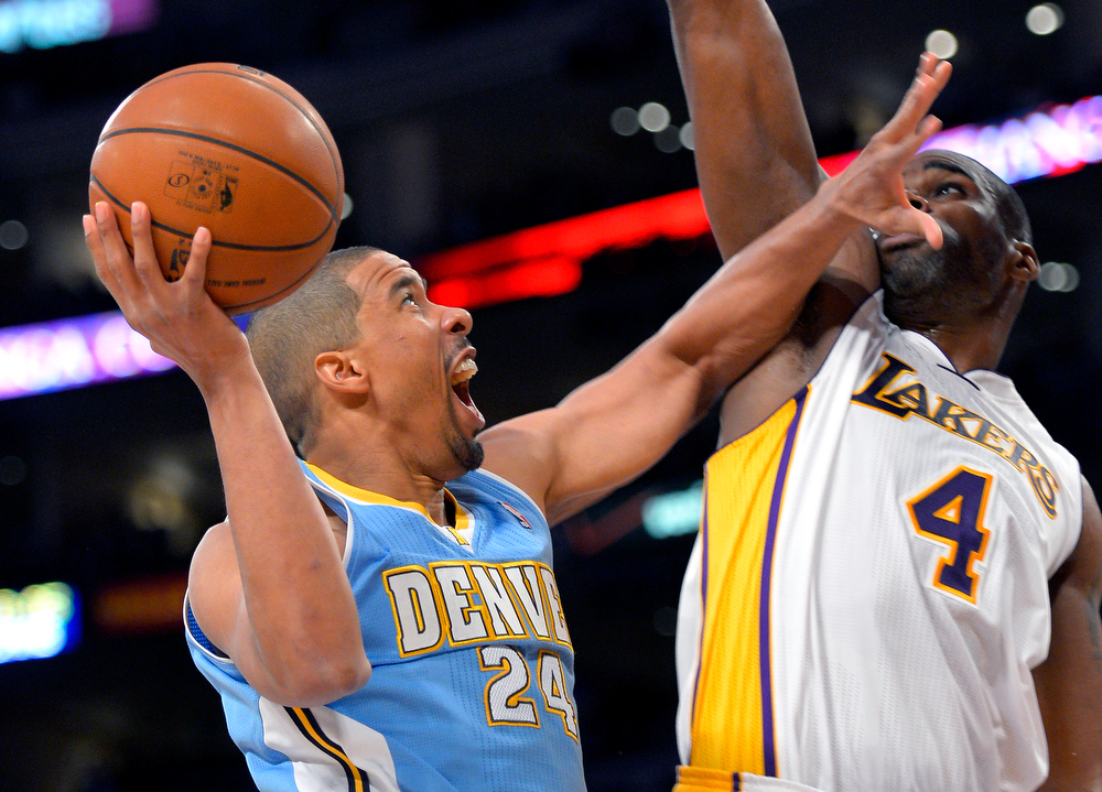 Description of . Denver Nuggets guard Andre Miller, right, shoots around Los Angeles Lakers forward Antawn Jamison during the first half of their NBA basketball game, Sunday, Jan. 6, 2013, in Los Angeles.  (AP Photo/Mark J. Terrill)