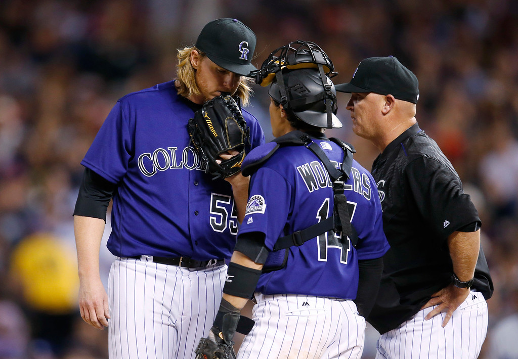 . Colorado Rockies starting pitcher Jon Gray, left, confers with catcher Tony Wolters, center, and pitching coach Steve Foster after giving up back-to-back hits to the Los Angeles Dodgers during the fifth inning of a baseball game Friday, April 22, 2016, in Denver. Colorado won 7-5. (AP Photo/David Zalubowski)