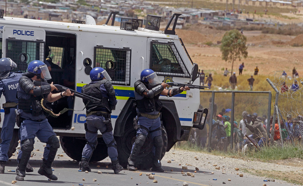 Description of . South African police fire rubber bullets at striking farm workers, right,  as they demonstrate in De Doorns , South Africa, Thursday, Jan 10, 2013. Striking farm workers in South Africa have clashed with police for a second day during protests for higher wages. The South African Press Association says police on Thursday fired rubber bullets at rock-throwing demonstrators in the town of De Doorns in Western Cape province, and protests were occurring in at least two other towns. (AP Photo/Schalk van Zuydam)