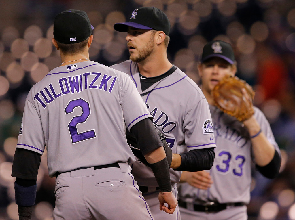 . Colorado Rockies relief pitcher Nick Masset, middle, talks with shortstop Troy Tulowitzki (2) and first baseman Justin Morneau (33) during the eighth inning of a baseball game against the Kansas City Royals at Kauffman Stadium in Kansas City, Mo., Tuesday, May 13, 2014. The Royals defeated the Rockies 5-1. (AP Photo/Orlin Wagner)
