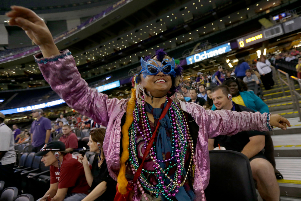 Description of . Jennifer Jones, of New Orleans, wearing Mardi Gras attire dances in the isles of the Superdome during media day for the NFL Super Bowl XLVII football game Tuesday, Jan. 29, 2013, in New Orleans. (AP Photo/Gerald Herbert)