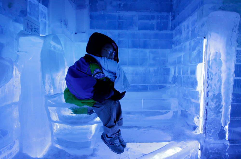 . A South Korean boy sits on the ice toilet at Ice Gallery in Seoul, South Korea, Tuesday, Aug. 3, 2010. The sweltering heat continues for the recent several days in Seoul. (AP Photo/ Lee Jin-man)