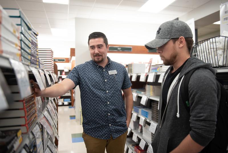 University Center Barnes & Noble employee Derrick Throndson (left) helps Michael Oejas find his textbooks.