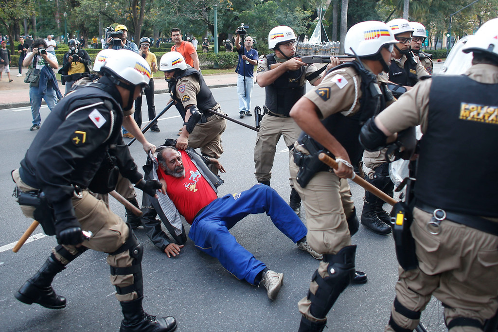 . Riot police detain a homeless man who was protesting against the 2014 World Cup in Belo Horizonte, Brazil, Thursday, June, 12, 2014. (AP Photo/Victor R. Caivano)