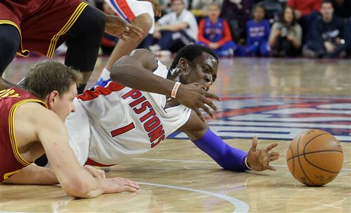 . Detroit Pistons guard Reggie Jackson (1) and Cleveland Cavaliers center Timofey Mozgov of Russia chase a loose ball during the second half of an NBA basketball game, Tuesday, Feb. 24, 2015 in Auburn Hills, Mich. Cleveland defeated the Pistons 102-93. (AP Photo/Carlos Osorio)