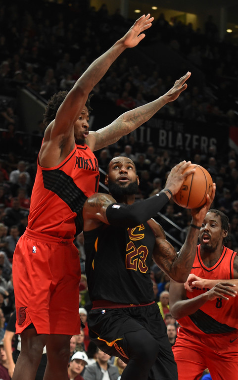 . Cleveland Cavaliers forward LeBron James, right, drives to the basket on Portland Trail Blazers forward Ed Davis, left, during the first half of an NBA basketball game in Portland, Ore., Thursday, March 15, 2018. (AP Photo/Steve Dykes)