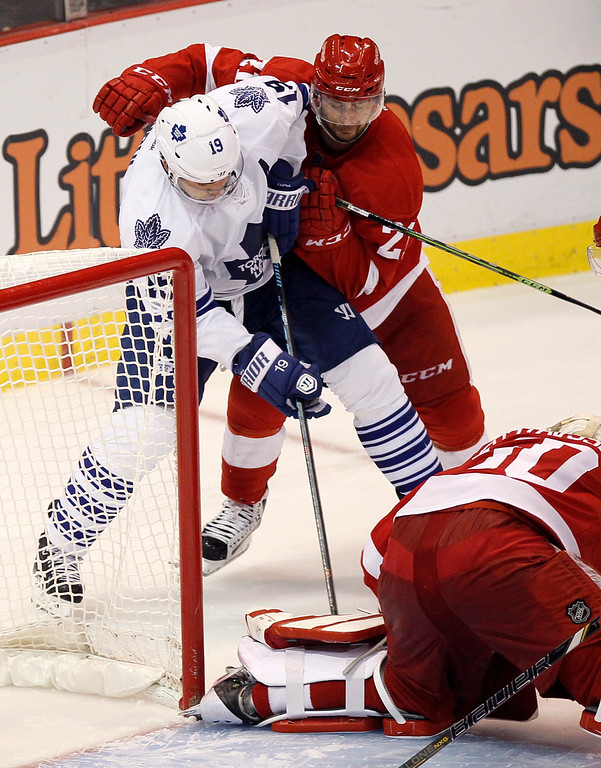 . Toronto Maple Leafs\' Joffrey Lupul is defended by Detroit Red Wings\' Tomas Tatar (21), of Slovakia, as Detroit Red Wings goalie Jonas Gustavsson (50), of Sweden, covers the puck during overtime of an NHL hockey games Saturday, Oct. 18, 2012, in Detroit. (AP Photo/Duane Burleson)