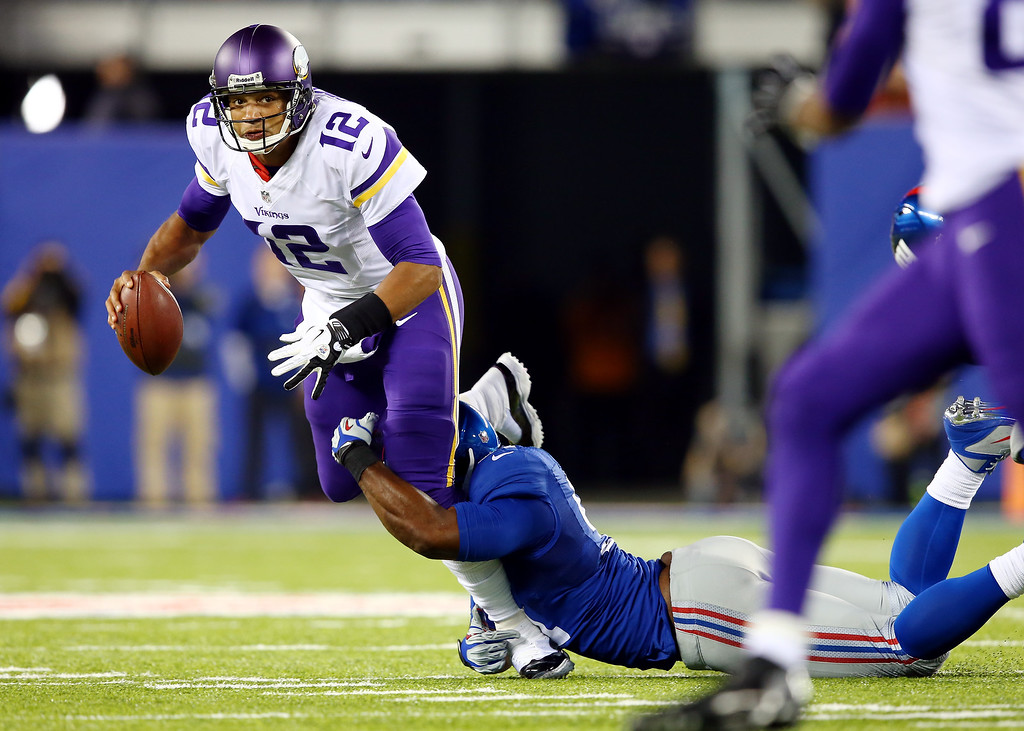 . Quarterback Josh Freeman #12 of the Minnesota Vikings is sacked by defensive end Justin Tuck #91 of the New York Giants during a game at MetLife Stadium on October 21, 2013 in East Rutherford, New Jersey.  (Photo by Elsa/Getty Images)