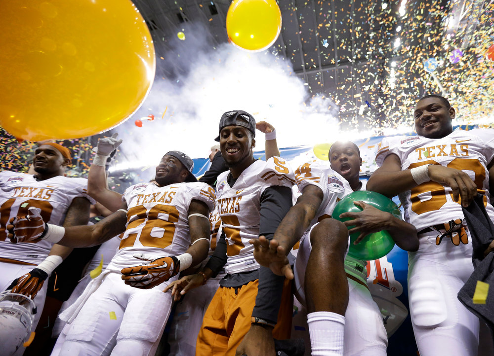 . Texas\' Marquise Goodwin, second from right, celebrates with teammates after defeating Oregon State in the Alamo Bowl NCAA football game, Saturday, Dec. 29, 2012, in San Antonio.  Texas won 31-27. (AP Photo/Eric Gay)