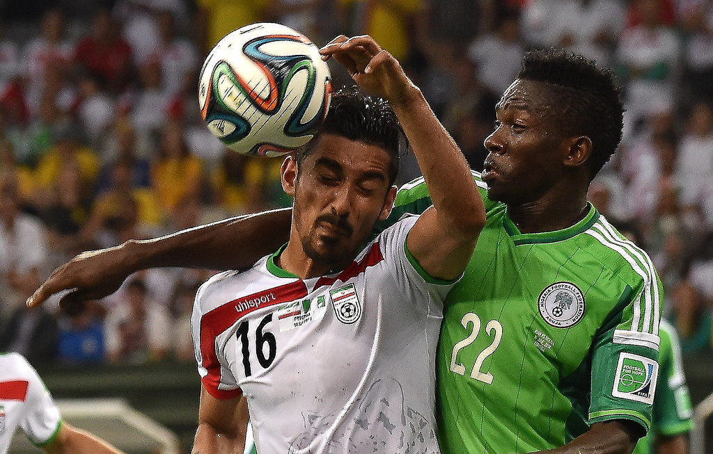 . Nigeria\'s defender Kenneth Omeruo (R) challenges Iran\'s forward Reza Ghoochannejhad during the Group F football match between Iran and Nigeria at the Baixada Arena in Curitiba during the 2014 FIFA World Cup on June 16, 2014.   LUIS ACOSTA/AFP/Getty Images