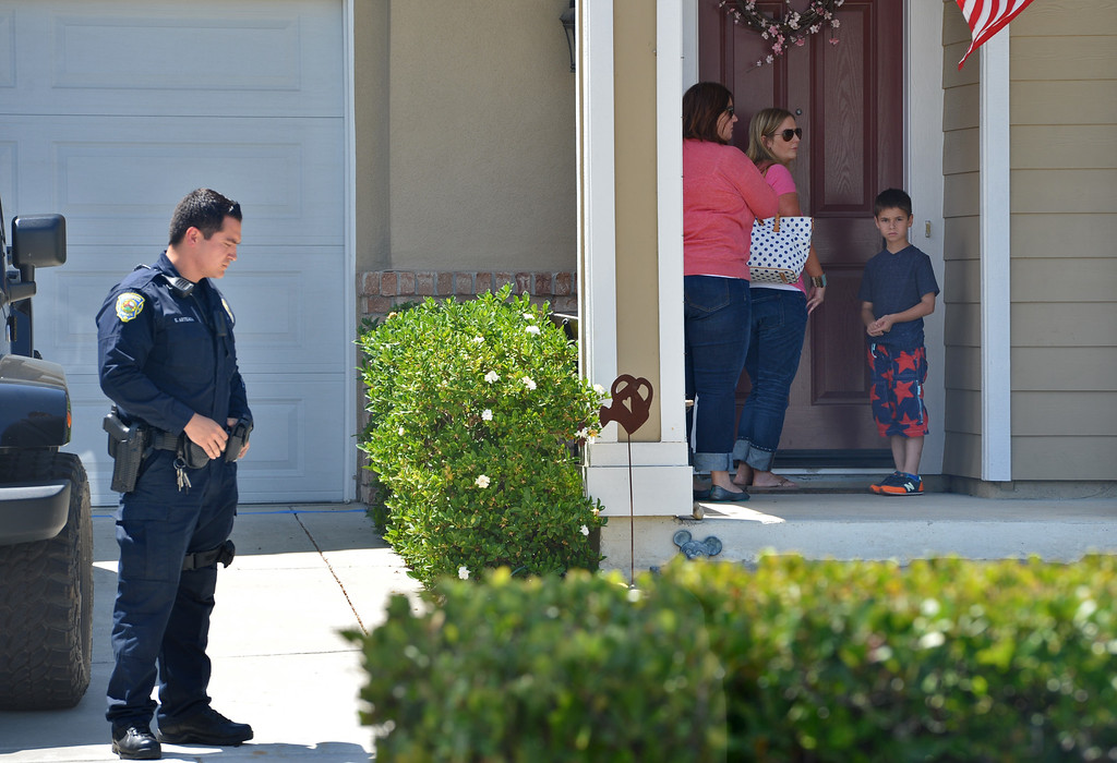 . A Brentwood police officer, left, guards the front of the home of Sgt. Scott Lunger of the Hayward Police Department, who was shot and killed early Wednesday morning after making a traffic stop on a driver who was driving erratically in Hayward, in Brentwood, Calif., on Wednesday, July 22, 2015. (Dan Rosenstrauch/Bay Area News Group)