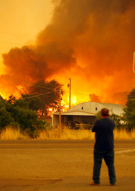 . Dean Smith watches as the Yarnell Hill Fire encroaches on his home in Glenn Ilah on Sunday, June 30, 2013 near Yarnell, Ariz. The fire started Friday and picked up momentum as the area experienced high temperatures, low humidity and windy conditions. It has forced the evacuation of residents in the Peeples Valley area and in the town of Yarnell. (AP Photo/The Arizona Republic, David Kadlubowski)