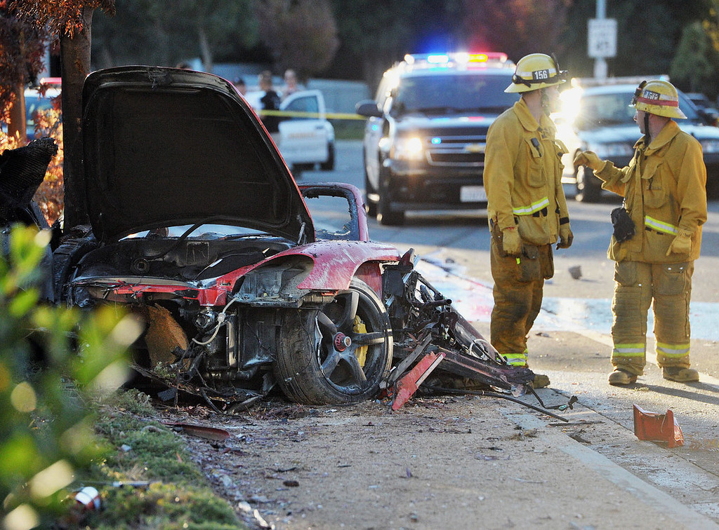 ". First responders gather evidence near the wreckage of a Porsche sports car that crashed into a light pole on Hercules Street near Kelly Johnson Parkway in Valencia on Saturday, Nov. 30, 2013. A publicist for actor Paul Walker says the star of the ""Fast & Furious\"" movie series has died in a car crash north of Los Angeles. He was 40. Ame Van Iden says Walker died Saturday afternoon. No further details were released. (AP Photo/The Santa Clarita Valley Signal, Dan Watson)"