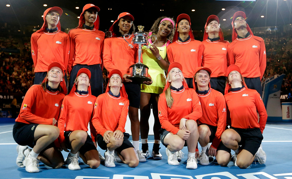 . Serena Williams of the U.S., holding the trophy, center, poses with ball kids  after defeating Maria Sharapova of Russia in the women\'s singles final at the Australian Open tennis championship in Melbourne, Australia, Saturday, Jan. 31, 2015. (AP Photo/Bernat Armangue)